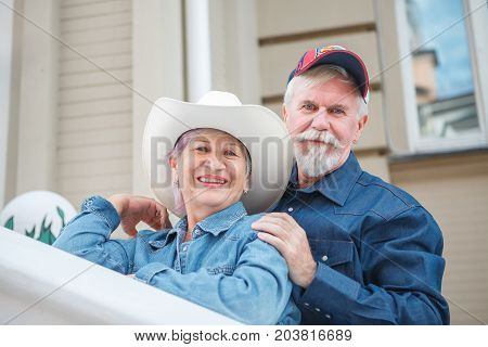 Happy friendly senior couple posing arm in arm with their faces touching smiling at the camera