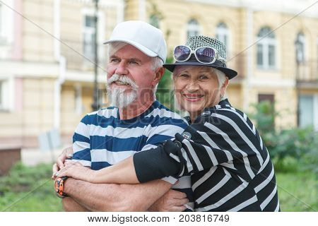 Loving Elderly Couple Posing On Camera. Pensioners Hug Each Other. Happy Old People.