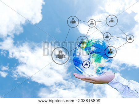 Terrestrial globe with networking system in male palm on abstract blue sky background. Elements of this image furnished by NASA
