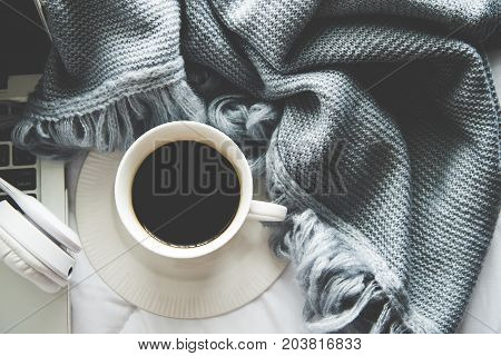 The laptop working and listen music on the white bed and coffee with marshmallow warm knitted sweater in the sunny day. Cozy winter home morning holiday. Music and Lifestyle Concept.