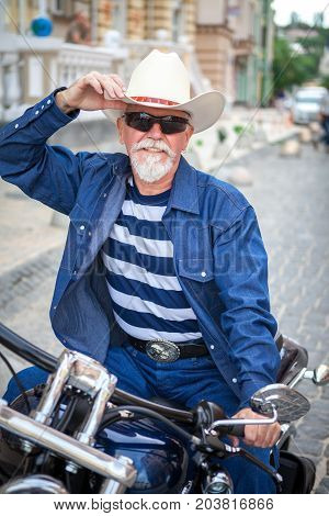 An elderly man in a cowboy hat is sitting on a motorcycle. A man on a motorcycle wearing a cowboy hat.