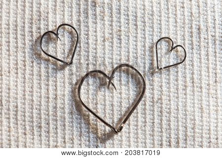Love of fishing heart of fish hooks. Close-up. Concept Wallpaper space for text. Heart Shape Made of Two Fish Hooks