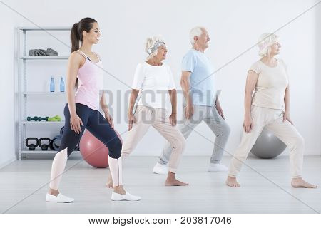 Elderly People Exercising With Trainer