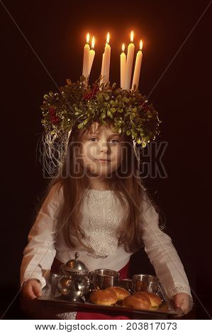 Little caucasian girl in Saint Lucia costume with crown of candles and traditional swedish sweet