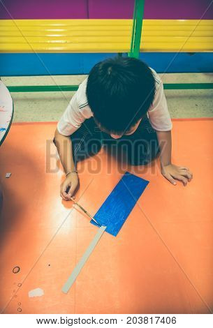 Happy Asian Boy Painting Blue Color On Artwork With Paintbrush.