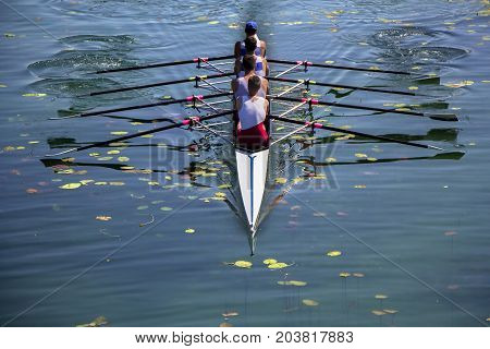 Males fours rowing team in race on the lake