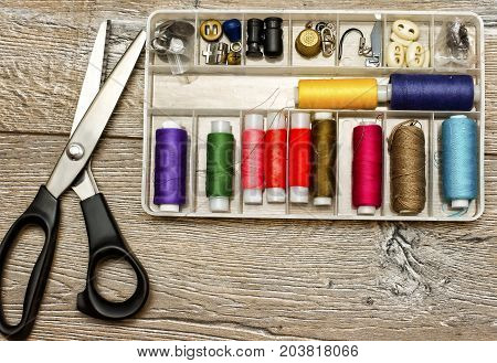 Sewing background: tailoring scissors,sewing toolbox and multicolor sewing threads on wooden table. Top view. Wooden texture.Template for designers