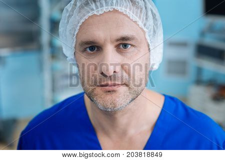 Look at me. Delighted male person pressing lips and posing on camera while being in sterile uniform