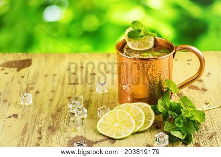 Moscow mule cocktail with mint, lime and vodka in copper mug. Summer drink on wooden background