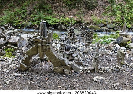 Balancing stones on the bank of a mountain river in the Carpathians. Towers pyramids and sculptures from river pebbles on the banks of the stream.