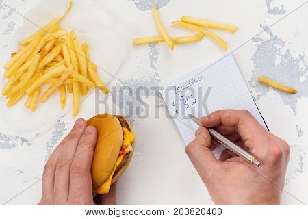 Man making to do list for tomorrow and eating unhealthy fast food today. Procrastination concept.  Top view. Selective focus