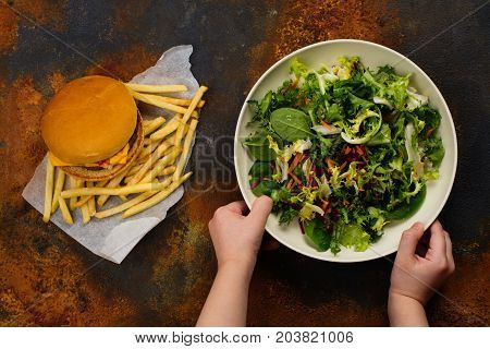 Child making choice between healthy salad and fast food. Choosing healthy meal instead of burger. Diet or healthy lifestyle concept