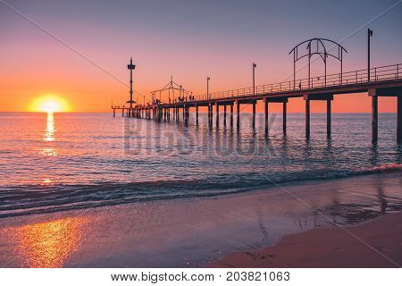 Brighton Beach pier with people at sunset South Australia
