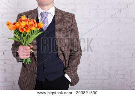 Business Man Holding Tulip Flowers Over White Wall