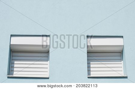 blue facade with two white windows down