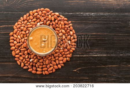 Peanut Butter On A Table In A Glass Jar Surrounded By Peanuts