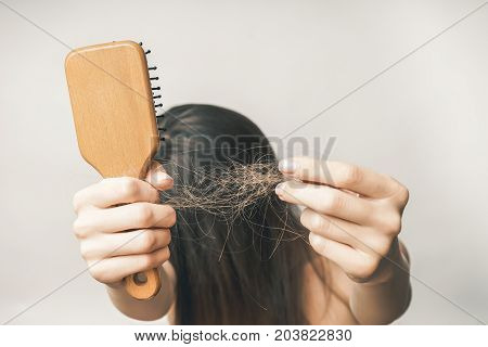 A young woman with long hair is annoyed with hair loss, holds a comb and her hair in her hand, hides her eyes