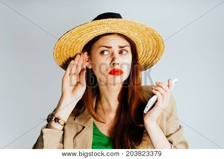 A young woman in a straw hat eavesdrops, looks wistfully to the left. Isolated on a gray background