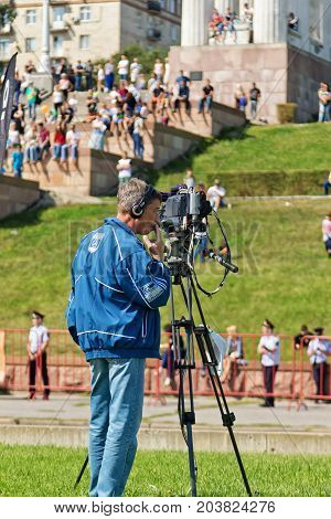VOLGOGRAD - SEPTEMBER 9: A journalist with a video camera on a tripod in the first championship of Russia on freestyle motocross. September 9 2017 in Volgograd Russia.