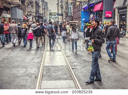 ISTANBUL TURKEY : Soap bubbles seller and walking people on Istiklal Avenue on October 6 2014. Istiklal is one of the most famous avenues in Istanbul visited by nearly 3 million people in a day