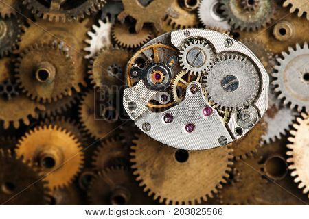 Aged clock mechanism macro view. Retro hand watches parts on bronze gears background.