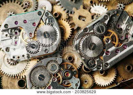 Vintage clocks mechanism close-up. Aged hand watches parts on bronze gears background.