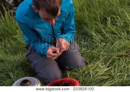 Young Man Decomposing Stem Of Nettle While Sitting Near Camping Stove.