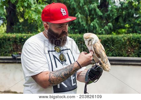 PRAGUE CZECH REPUBLIC - JUNE 26 2017: Bearded caucasian hipster man in red full cap with tattoo on his arms holds an owl in hand in summer time on the street in Prague Czech Republic