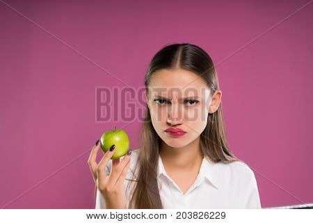 A young woman doctor dissatisfiedly eats an apple, looks angrily at the camera, holds a folder with papers in her hands. Isolated on a pink background