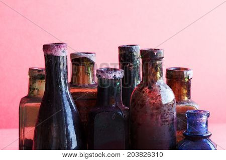 Retro design bottles macro view. Colorful dirty glass flacon set. Pink background, shallow depth of field, copy space