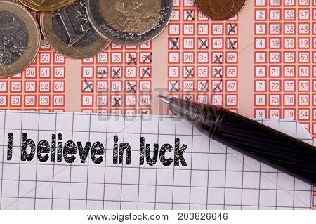 I believe in luck. Pen and bingo lotto lottery ticket with crossed numbers.