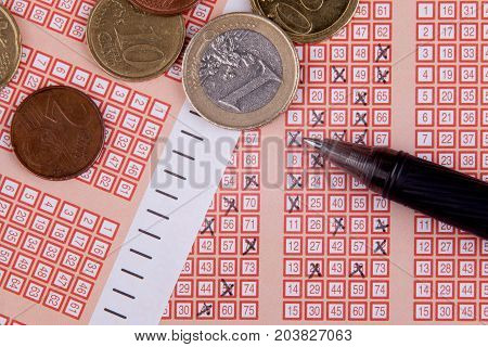 pen and bingo lotto lottery ticket with crossed numbers, euro money.