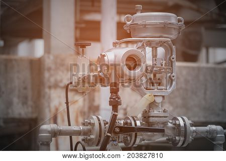 Flow control valve in petrochemical plant on blurred background