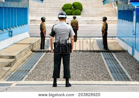 PANMUNJOM, SOUTH KOREA - SEPTEMBER 26, 2014: Korean soldiers watching border between South and North Korea in the Joint Security Area (DMZ) on September 26, 2014 in Panmunjom, South Korea