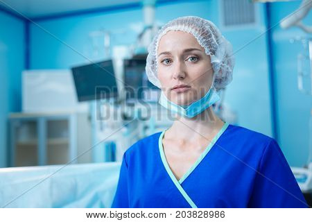 We did it. Competent medical worker taking off her mask and opening mouth while standing in operating room