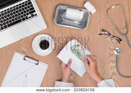 Cropped image of doctor talking money from his patient.