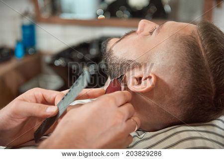 Close up shot of a young bearded man sitting relaxed at the barbershop while professional barber trimming his beard.