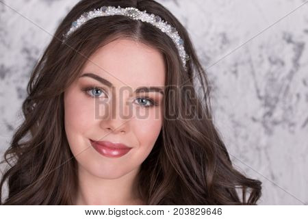 Beautiful woman in diadem and with hairdo poses in white studio close-up poster