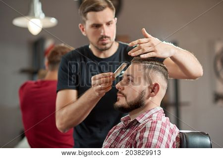 Portrait of a young barber styling hair of his bearded client.