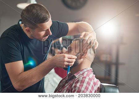 Professional barber working shaving his bearded client at the barbershop.