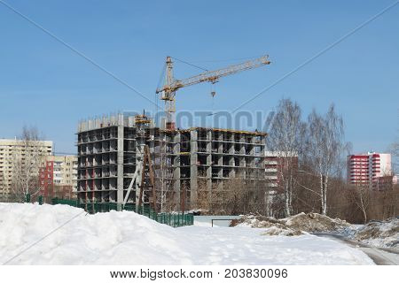 Unfinished high-rise apartment building and crane at snowy winter day