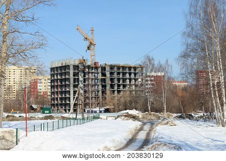 Unfinished high-rise apartment building and working crane at snowy winter day
