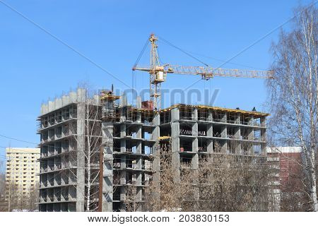 Unfinished high-rise apartment building and crane at sunny winter day