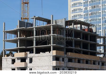 Unfinished high-rise apartment building part of crane at sunny day