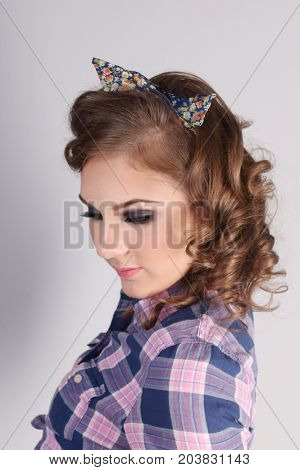 Pinup beautiful girl in checkered shirt with closed eyes in studio