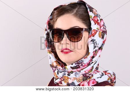 Beautiful smiling young woman in sunglasses and shawl in grey studio