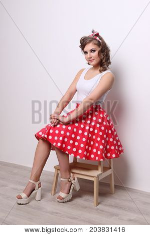 Pinup beautiful girl in red skirt poses on wooden stool in studio