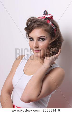 Pinup beautiful girl in white and with curly hair poses in white studio
