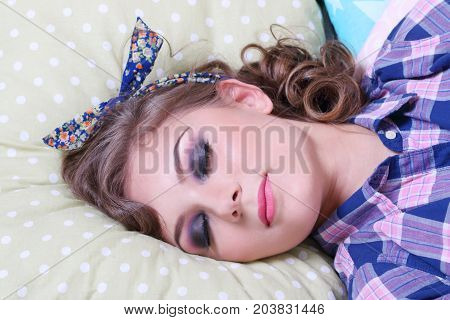 Pinup pretty girl in checkered shirt sleeps on soft pillows in studio