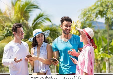 Group Of Young People Talking Holding Cell Smarrtphones Over Green Tropical Forest Landscape Mix Race Men And Women Communicating Using Modern Telephones